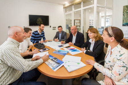 Team of expert real estate agents in Altea sitting around meeting table
